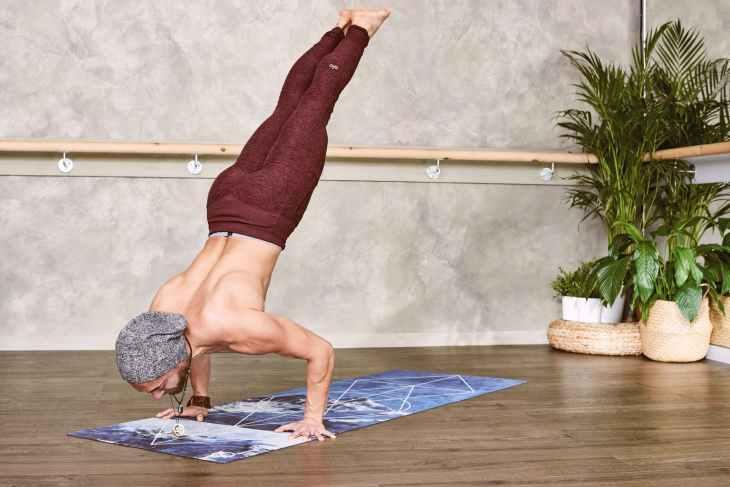 man wearing brown leggings doing yoga pose inside room